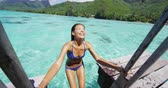 nadador : Vacation girl swimming in ocean tropical paradise destination luxury travel. Bikini woman coming out from swim enjoying holidays on overwater deck at hotel resort, Tahiti, French Polynesia. Stock Footage