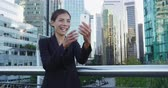 acenando : Video chat business meeting concept. Businesswoman talking or vlogging using smart phone app on smartphone for social media smiling happy wearing suit jacket outdoors. Urban female professional. Stock Footage