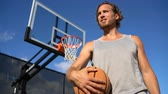 tribunal : Basketball Player. Tired man holding basketball against blue sky. Young male is looking away on sunny day. He is standing at basketball court outside.