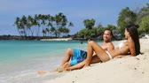koupání : Vacation travel couple relaxing on beach talking laughing having fun. Happy multiethnic man and woman are lying on sand during summer vacation. They are enjoying on sunny day. Dostupné videozáznamy