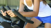 велосипед : Fit woman using exercise bike at gym. Young female is exercising at fitness health club. She is wearing tank top and shorts.