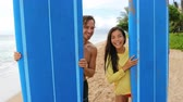 выглядывал : Surfing happy man and woman peeking through blue surfboards at beach. Smiling multiethnic couple are enjoying summer vacation.