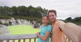 New Zealand tourist attraction couple tourists taking selfie at famous travel destination, Waiotapu. Active geothermal yellow pond, Rotorua, north island. AKA Wai-O-Tapu, New Zealand. Stock Footage