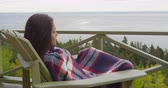 envolto : Relaxed young woman wrapped in blanket sitting on chair at balcony outside in forest cabin by the sea in Fall. Relaxing woman in pensive mood is resting enjoying sea view during autumn. Vídeos