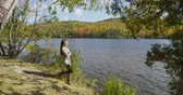 листва : Young woman in fall walking with enjoying serene forest foliage by lake during Autumn. Female tourist is looking at autumn trees on mountain by lake. She is enjoying natures view during vacation.