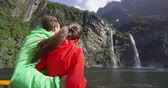 wróżka : Cruise ship tourists on boat tour in Milford Sound, Fiordland National Park, New Zealand. Happy couple on sightseeing travel sailing by fairy falls waterfall on New Zealand South Island. SLOW MOTION. Wideo