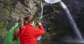 wróżka : Cruise ship tourists taking photos using phone on boat tour in Milford Sound, Fiordland National Park, New Zealand. Couple sightseeing travel sailing by fairy falls waterfall on New Zealand.