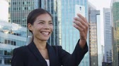 saying : Video chat business meeting concept. Businesswoman talking or vlogging using smart phone app on smartphone for social media smiling happy wearing suit jacket outdoors. Urban female professional. Stock Footage