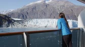 varanda : Glacier Bay Alaska cruise ship passenger looking at glacier in Glacier Bay National Park, USA. Woman on travel sailing Inside Passage enjoying luxury stateroom balcony with view of Margerie Glacier. Stock Footage