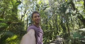 pântano : Man taking selfie video hiking in New Zealand looking at camera in swamp forest nature landscape in Ship Creek, West Coast of New Zealand. Happy tourist hiker sightseeing New Zealand Stock Footage