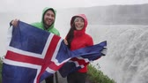 elmas : Travel tourists fun by Dettifoss waterfall on Iceland showing Icelandic flag. People visiting famous tourist attractions and landmarks on Diamond Circle. Happy tourist couple enjoying vacation travel.