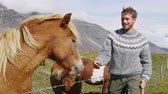 local : Icelandic horses - man petting horse on Iceland. Man in Icelandic sweater going horseback riding smiling happy with horse in beautiful nature on Iceland. Handsome Scandinavian model. 90 FPS. Vídeos