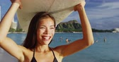 waikiki : Happy young woman carrying surfboard on head at Waikiki Beach. Beautiful female tourist is walking on shore during summer vacation at island in Honolulu. She is enjoying by sea against sky. Stock Footage