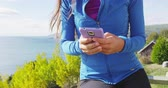mobile game : Phone app in autumn fall nature - woman close up of smartphone. Girl using cellphone in sporty running fitness clothing by sea and mountain forest landscape.