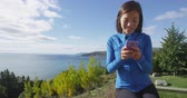 tenue : Woman using phone app in autumn fall nature - smartphone concept. Girl using cellphone in sporty running fitness clothing by sea and mountain forest landscape.