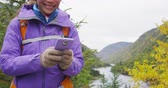 excursionistas : Woman using phone app in nature. Person hiking in fall using smartphone app with touch screen tech gloves during hike in autumn travel adventure in mountain forest outdoors. Beautiful landscape.