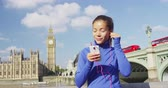 марафон : London woman runner listening to music on phone using by Big Ben and Westminster Bridge, London, England, UK.
