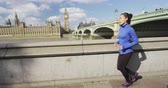 westminster : Running woman runner jogging in London by River Thames and Westminster Bridge. SLOW MOTION. Stock Footage