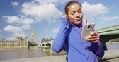 reino unido : London lifestyle woman runner listening to music on smart phone near Big Ben. Female running girl resting after training in city. Fitness girl smiling happy on Westminster Bridge, London, England, UK. Stock Footage