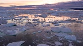 jakobshavn : Arctic nature landscape with icebergs in Greenland icefjord with midnight sun sunset  sunrise in the horizon. Aerial drone footage video of ice. Ilulissat Icefjord with icebergs from glacier.