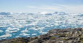 groenland : Travel in arctic landscape nature with icebergs - Greenland tourist man explorer - tourist person looking at amazing view of Greenland icefjord - aerial video. Man by ice and iceberg in Ilulissat.