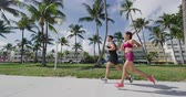разработка : Couple running jogging exercising on South Beach, Miami, Florida, in Art Deco District. Man and woman runners working out together. Lifestyle video in SLOW MOTION shot on RED Cinema Camera. Стоковые видеозаписи