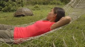 riese : Ecotourism Travel adventure on Galapagos Islands, - tourist woman relaxing in hammock by Giant Tortoise Santa Cruz Island in Galapagos Islands.