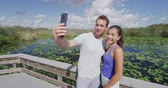 turistler : Everglades National Park - tourist couple taking phone selfie photo visiting Florida Everglades. Couple on travel vacation walking Anhinga Trail. Shot on RED in SLOW MOTION. Stok Video