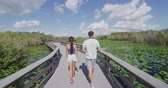 turistler : Everglades National Park Trail - tourists visiting Florida Everglades. Couple on travel in Miami doing day tour to Everglades walking Anhinga Trail. RED EPIC SLOW MOTION. Stok Video