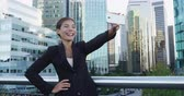 distrito : Smiling young businesswoman taking selfie with mobile phone against office buildings. Beautiful female professional is using smart phone in financial district. She is wearing suit in city.