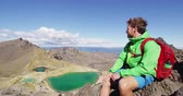tongariro : New Zealand Travel - Hiking man enjoying the view from summit of Emerald Lakes. Backpacker hiking on Tongariro Alpine Crossing. Spectacular landscape, Tongariro National Park, New Zealand. SLOW MOTION Stock Footage
