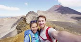 tongariro : Young couple hiking taking selfie video at hike Tongariro Alpine Crossing. Smiling healthy backpackers photographing themselves in mountains. Beautiful landscape in Tongariro National Park New Zealand