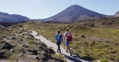 tongariro : Couple Backpacking Hiking and Walking On Tramping Track on New Zealand in Tongariro National Park. Romantic couple Man and woman holding hands in mountains. Couple on hike in Tongariro Alpine Crossing