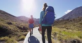 tongariro : Adventure - Hiking people tramping on trail in Tongariro Alpine Crossing, a National Park in New Zealand, North Island. Male and female hikers couple hiking by Mount Ngauruhoe. RED EPIC SLOW MOTION. Stock Footage