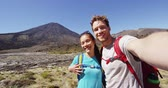tongariro : Happy Backpacking Couple Taking Selfie Video on Travel on New Zealand Hiking Tongariro Alpine Crossing. Couple photographing themselves by volcano. Beautiful landscape in Tongariro National Park. Stock Footage
