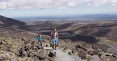 krater : Young man and woman hiking wearing backpacks walking in amazing volcanic landscape in New Zealand. Couple backpackers hiking in Tongariro National Park. Stunning landscape, Tongariro Alpine Crossing.