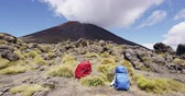 tongariro : Hiking Travel Adventure Concept. Red and blue hiking backpacks on volcanic landscape at Tongariro National Park. Hike gear equipment with Mount Ngauruhoe volcano mountain, New Zealand.