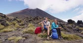 hidratar : Hiking couple relaxing on hike drinking water taking break on Tongariro Alpine Crossing, New Zealand. Happy people on travel vacation on North Island, New Zealand. SLOW MOTION.