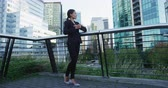 pacing : Low-angle full length view of young Asian businesswoman in black suit standing with on balcony over cityscape background with arms crossed and looking away thoughtfully. Copy space Stock Footage