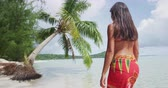 nativo : Travel woman walking on paradise beach on holidays vacation on Matira Beach, Bora Bora. Happy joyful girl on holidays beach vacation wearing traditional pareo and Bikini in Tahiti, French Polynesia.