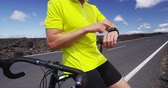 dostihy : Athlete cyclist using a smartwatch activity tracker gps smartwatch during biking workout training. Road bike sports man using his smart watch app for fitness tracking. Healthy lifestyle SLOW MOTION.