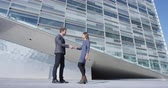 shaking hands : Business Handshake - business people meeting shaking hands. Handshake between business man and woman outdoors by office building. Casual clothing, young people, 30s. shaking hands closeup. SLOW MOTION Stock Footage
