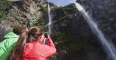 fadas : Cruise ship tourists taking photos using phone on boat tour in Milford Sound, Fiordland National Park, New Zealand. Couple sightseeing travel sailing by fairy falls waterfall on New Zealand.