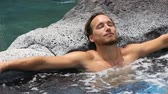 retreat : Spa wellness - man relaxing in hot tub whirlpool jacuzzi outdoor at luxury resort spa retreat. Happy young male model relaxed resting in water on vacation travel holidays. Stock Footage