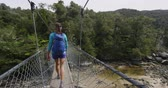 suspensão : Hiking. Woman tramping in New Zealand, Abel Tasman National Park. Young traveller backpacking crossing swing bridge over Falls River. Shot in SLOW MOTION.