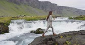 ring road : Happy woman walking by waterfall on Iceland. Girl tourist in casual clothing visiting icelandic nature landscape Stock Footage