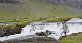 возбужденный : Woman walking by waterfall on Iceland. Girl tourist in casual clothing visiting icelandic nature landscape. RED EPIC SLOW MOTION.