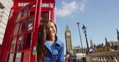 saying : London. Happy woman waving while coming out of phonebooth in London. Young female is having fun her vacation in London by Big Ben famous tourist attraction destination landmark. England. Stock Footage
