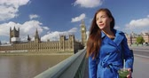 westminster : Woman walking on Westminster Bridge by famous destination Big Ben and Parliament Building. Young Female professional business woman in blue trench coat Stock Footage