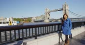 tamisa : Business woman walking by London Tower Bridge. Smiling businesswoman or tourist walking by River Thames looking away while enjoying view of famous landmark in United Kingdom.